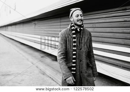 Portrait of cheerful young man in a gray coat and a hat outdoors. Black and white portrait of cheerful hipster outdoors ** Note: Soft Focus at 100%, best at smaller sizes