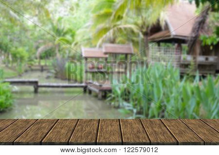 wooden bridge across the pond and thailand traditional house in the garden (blur background with wood table top for display or montage your product)