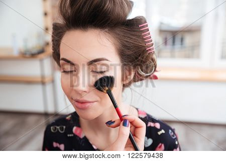 Makeup artist applying professional brush for face of young woman in curlers in beauty salon