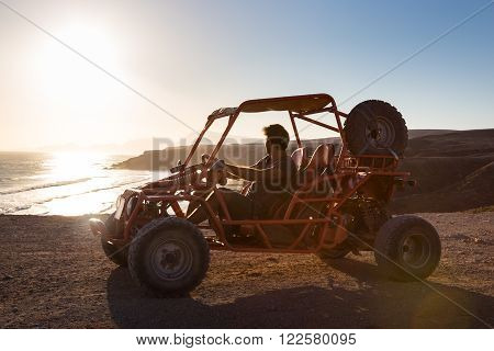 Active man driving quadbike on dirt road by the sea in sunset.