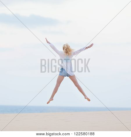 Relaxed woman enjoying freedom, feeling happy. Serene relaxing woman in pure happiness and elated enjoyment, jumping with arms outstretched up. Copy space for text.