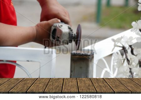 The worker use metal grinding wheel to grind the iron pole (blur background with wood table top for display or montage your product)