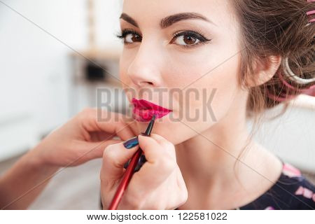 Makeup artist applying bright pink lipstick to lips of young woman in curlers