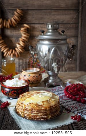 Traditional russian pancakes with cottage cheese, milk, bagels and samovar on vintage wooden background