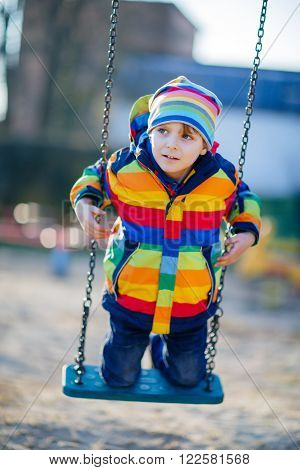 Little kid boy of 5 having fun with chain swing on outdoor playground. child swinging on warm sunny spring or autumn day. Active leisure with kids. Boy wearing colorful clothes