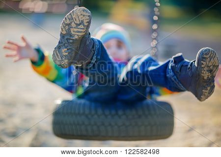 Funny kid boy having fun with chain swing on outdoor playground. child swinging on warm sunny spring or autumn day. Active leisure with kids. Selective focus