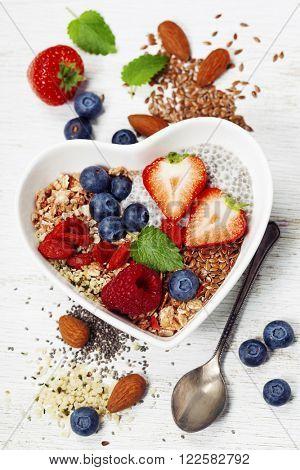 Healthy breakfast of muesli, berries with yogurt and seeds on white background -  Healthy food, Diet, Detox, Clean Eating or Vegetarian concept.Top view