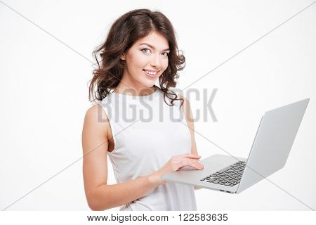 Smiling woman using laptop computer isolated on a white background and looking at camera