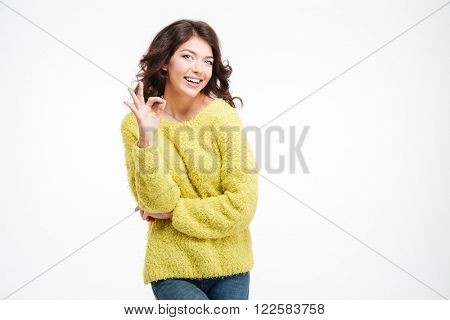 Portrait of a smiling woman showing ok sign with fingers isolated on a white background