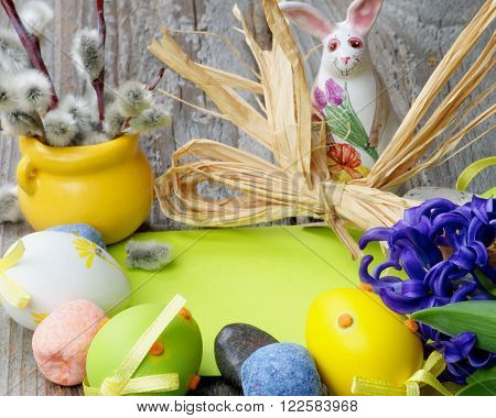 Easter Greeting Concept with Pussy-Willow Ceramic Bunny Colored Stones Crocus Easter Eggs and Empty Green Place to Congratulations closeup on Wooden background