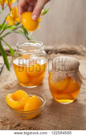 Organic canned peaches in glass jars with compote on vintage cloth background