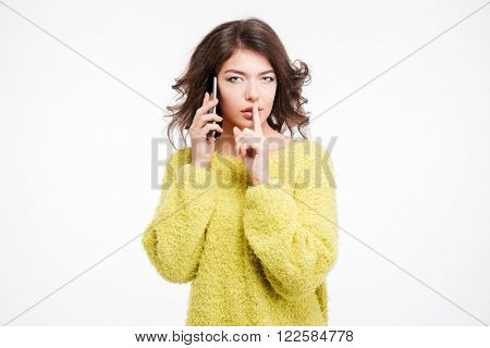 Woman talking on the phone and showing finger over lips isolated on a white background