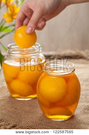 Natural peach compot in glass jars, healthy preserved dessert on vintage wooden table