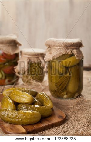 Pickled cucumbers in glass jars traditional salted homemade marinated vegetables on vintage table background