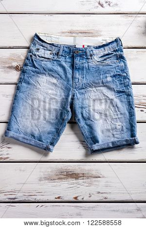 Female jeans shorts for summer. Woman's jeans shorts on shelf. Simple folded jeans shorts. Element of summer collection.