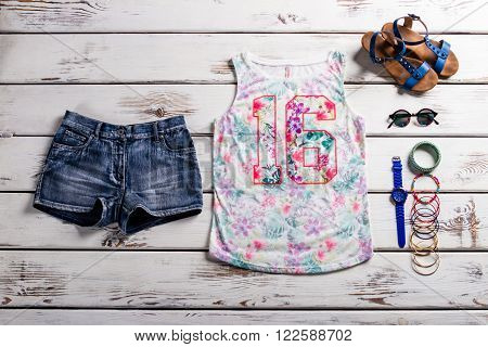 Lady's outfit with jeans shorts. Woodern showcase with female outfit. Casual outfit for teenage girls. Colorful tank top and accessories.