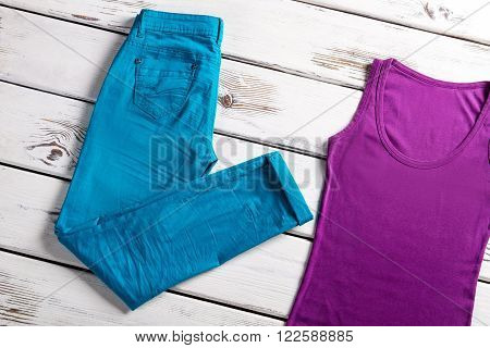 Bright female top and pants. Jeans and top on showcase. Woman's stretch jeans and top. Lady's colorful clothing for summer.