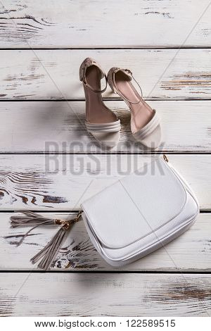 Small leather purse and footwear. Woman's shoes on old shelf. Accessory and footwear for ladies. Combination of shoes and purse.