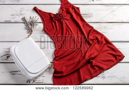 Red dress and leather purse. Handbag with dress on shelf. Elegant evening dress and accessory. Beautiful but not expensive.