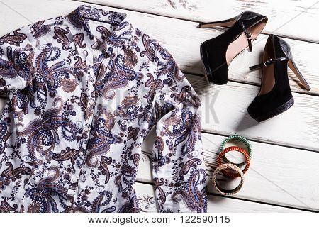 Floral shirt and coloful bracelets. Woman's clothing on wooden floor. Trendy footwear and nice shirt. Style of modern women.