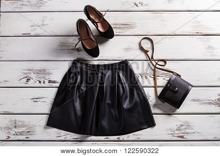 Leather skirt and suede shoes. Skirt and footwear on shelf. Fashionable clothes for modrn girls. Lady's trendy evening clothes.
