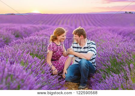 Romantic wedding couple in love in lavender fields, marry in Provence, France. Beautiful young groom and bride hugging at sunset.