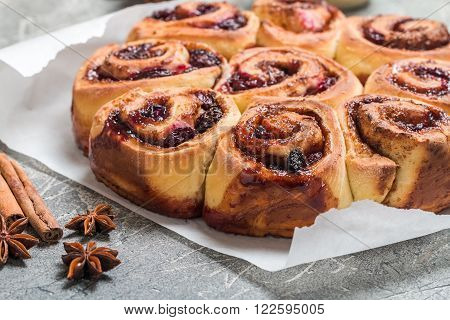 Cinnamon buns with lemon blueberry and thyme on gray background
