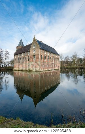 Dutch medieval castle built in 1474 reflected in the mirror smooth water surface of the moat on a beautiful day at the beginning of the spring season.