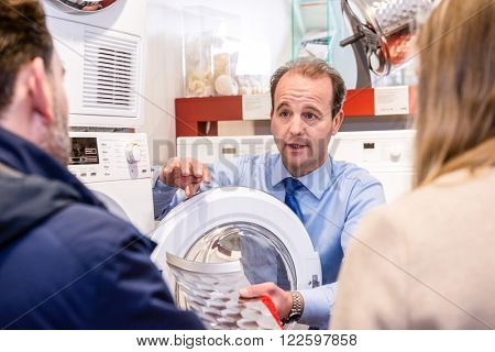 Salesman explaining product to couple in washing machine department of hypermarket