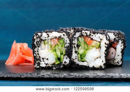 Japan black tobiko rolls with cream cheese and cucumber served with ginger on black board copyspace