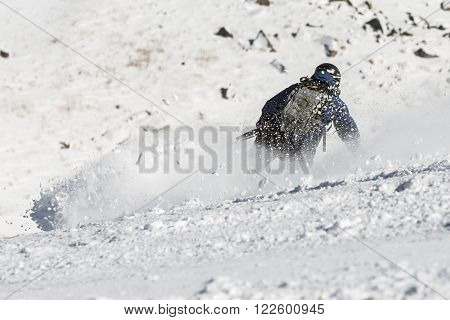A free rider is skiing down a snowy rocky mountain top. A picture from his back. High speed.