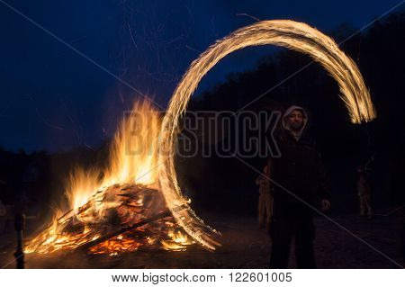 Sofia Bulgaria - March 13 2016: An young man is participating in a fire ritual during a celebration of Sirni Zagovezni. It is believed that evil spirits are chased away with this fire rituals.