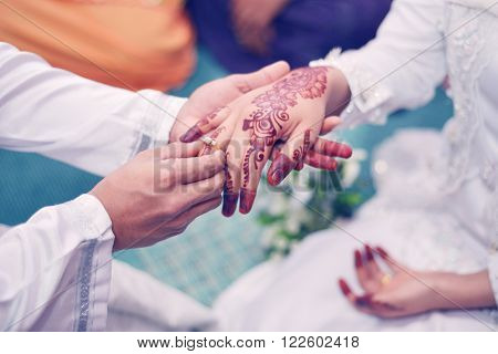 Malay Wedding Couple Putting A Gold Ring On Hand.Selective Focus And Shallow DOF.