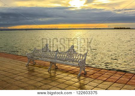Iron bench on the waterfront of the La Paz, Mexico, Baja California Sur, at sunset.