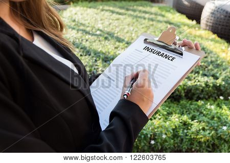 Businesswoman signing a insurance policy on the street.