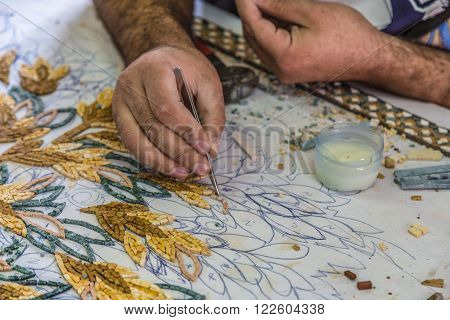 Madaba, Jordan - October 27, 2015: Artisan make artistic mosaics. Madaba is best known for its Byzantine mosaic. Mosaic in Jordan is the ancient national craft. The pattern shows a close-up.