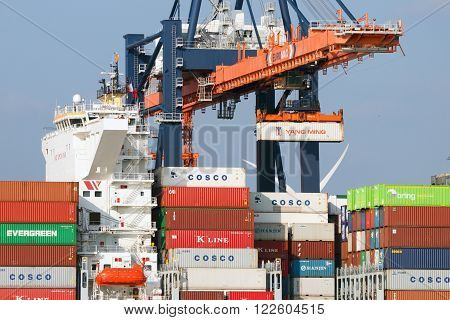 ROTTERDAM - MAR 16 2016: Crane operator placing a container in a cargo ship the Port of Rotterdam.
