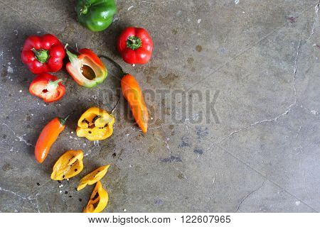 Overhead view of colorful whole and sliced hot peppers on a stone slab with room for text