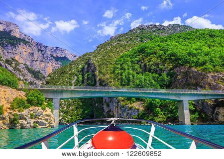 Travel to Provence. Bridge over the azure water of the river Verdon. Pleasure boat with the red lantern
