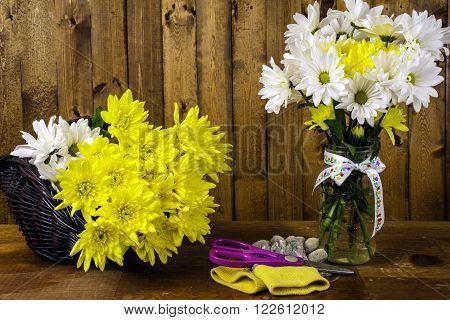 basket fresh cut flowers bouquet in glass mason jar scissors on work gloves wood background