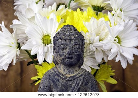 Buddha statue in front of bouquet of flowers with wood background