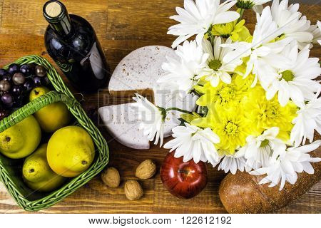 picnic basket with fruit cheese bread wine nuts and flowers on wood background