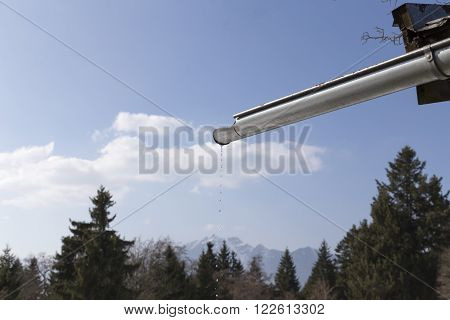A dripping gutter in the alps on a barn with the mountains in the background