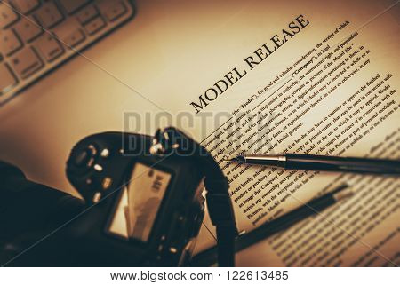 Model Release Documents with Elegant Pen and Part of Camera. Photography Business Legal Concept.