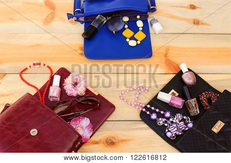 Cosmetics and women's accessories fell out of different handbag. Things from open lady handbag.
