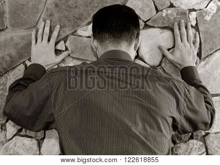 White man in a striped shirt stands with his back with his hands on the wall of stone. black white toning, shallow depth of field. the concept of police searches, arrest