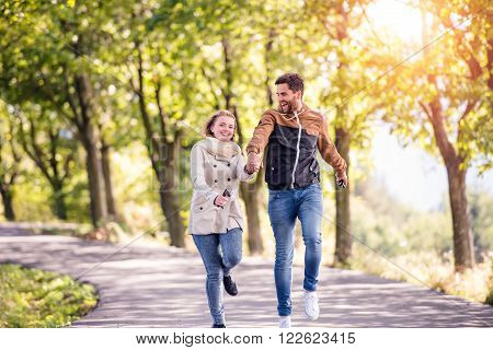 Smiling couple in love  in autumn sunny nature on a walk, running, holding hands, against green trees