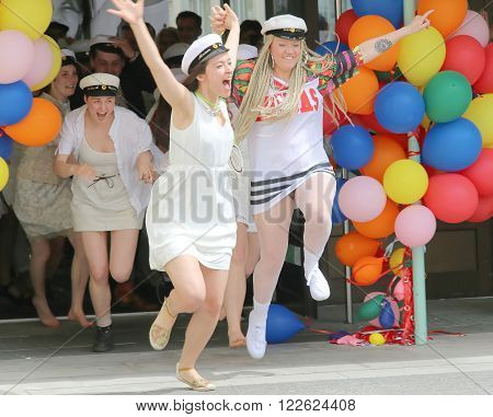 STOCKHOLM SWEDEN - JUN 10 2015: Group of happy teenage girls wearing graduation caps running out from the school door after graduation from high school at the school Globala gymnasiet June 10 2015 Stockholm Sweden