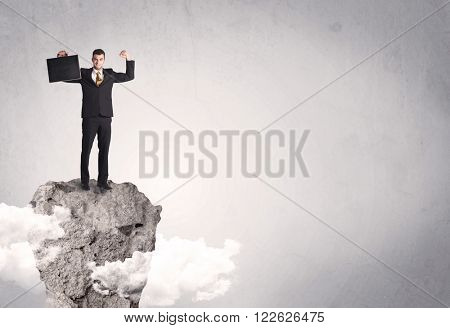 A happy successful businessman standing on a stone cliff with clouds in front of clear empty grey background concept