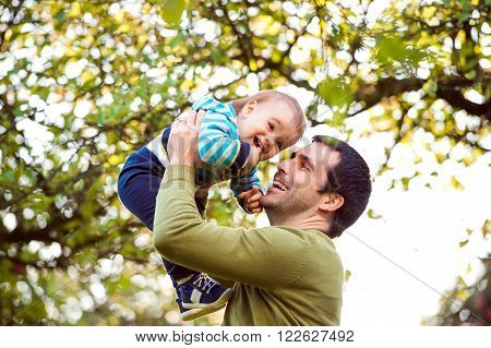 Father holding his little son, throwing him in the air, green tree